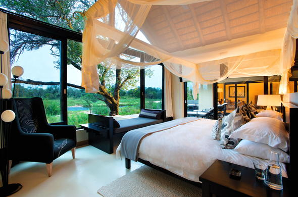 Sleep comfy in the luxury bedroom at Lion Sands Ivory Lodge.